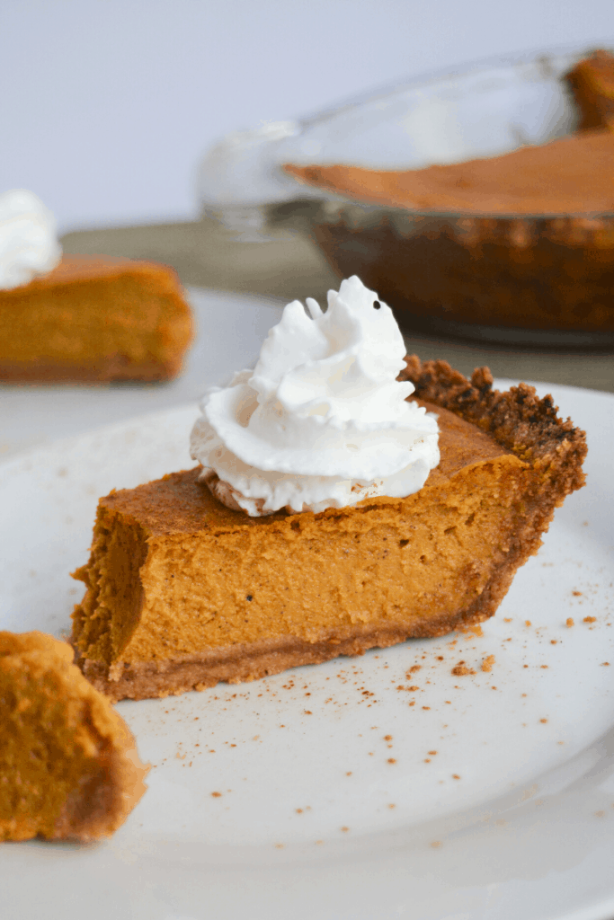 slice of keto pumpkin pie with a dollop of whipped cream on top