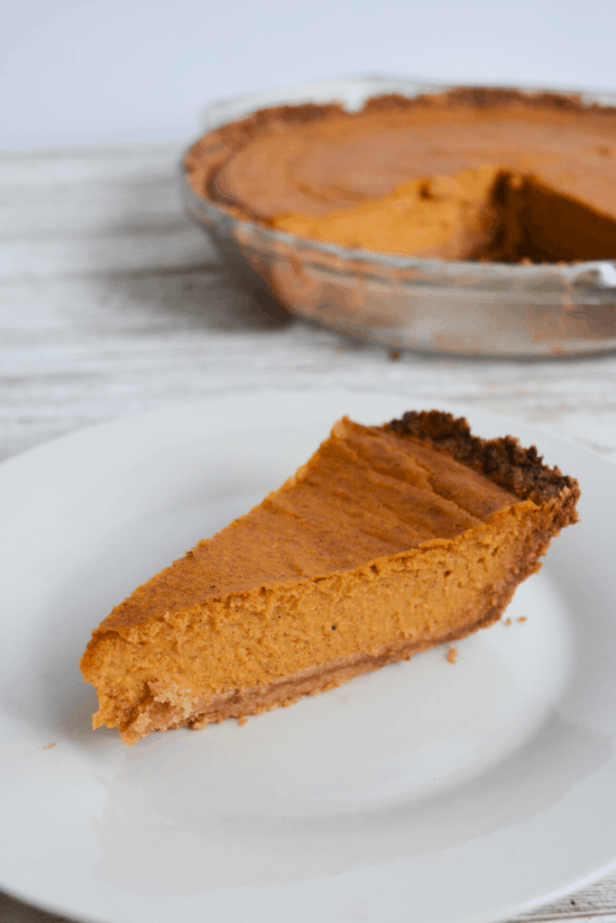 slice of pumpkin pie on white plate with full pie in the background