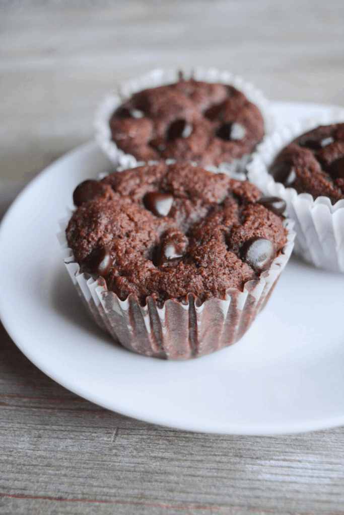 three double chocolate muffins sitting on a white plate