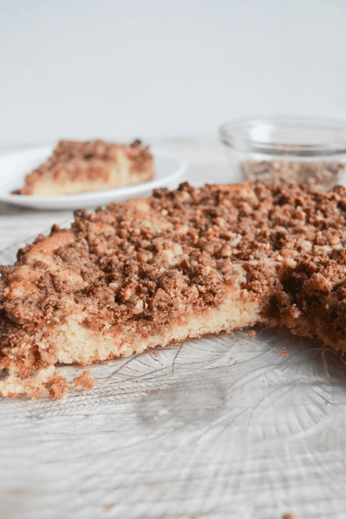 coffee cake sitting on a decorative glass plate, cut to show moist inside texture