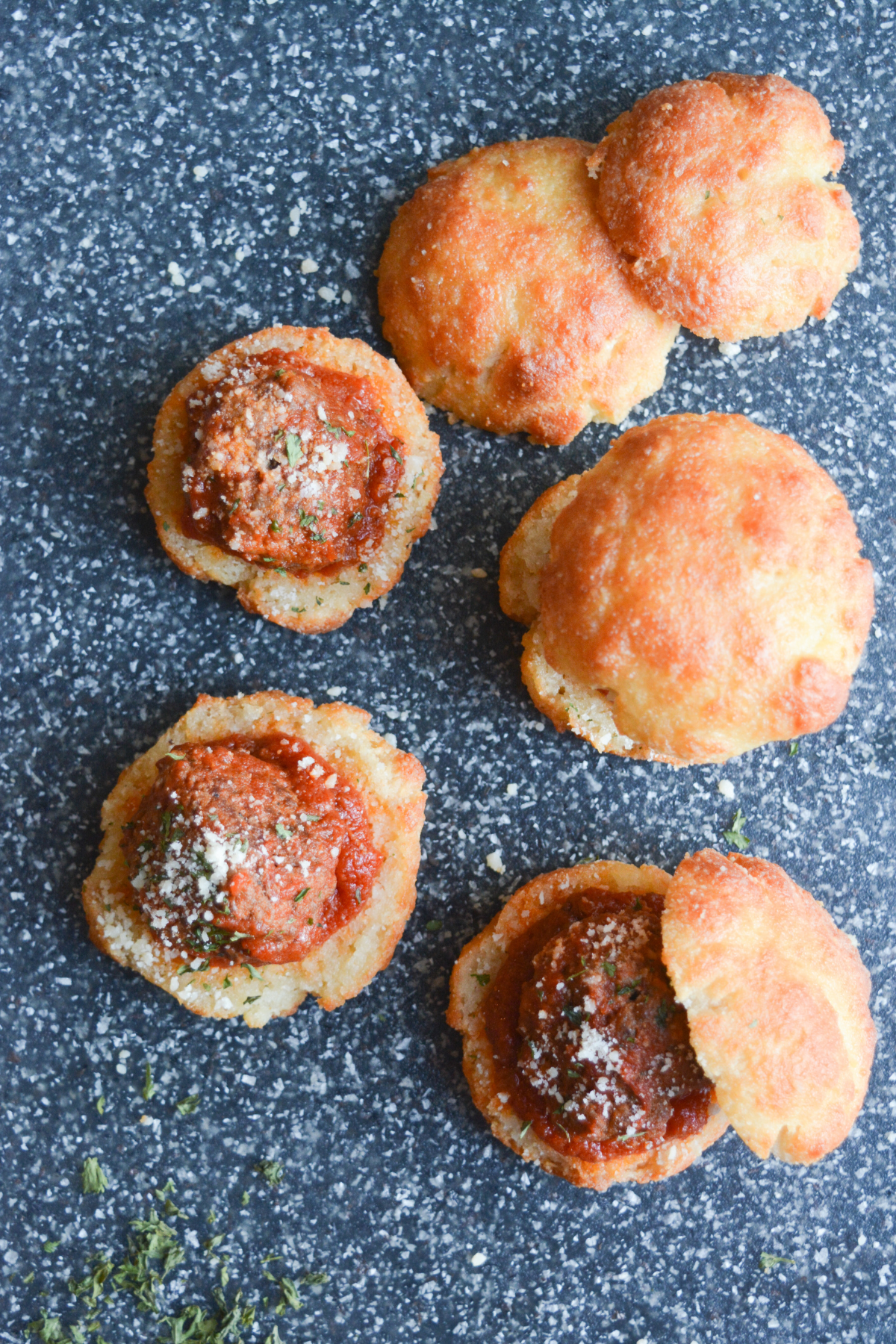 overhead shot of several garlic bread meatball sliders, showing the seasoned meatballs covered in parmesan cheese