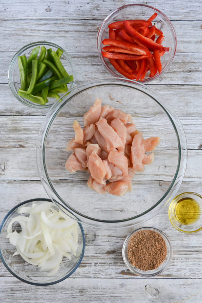 chicken fajitas ingredients, including sliced chicken breast, sliced red bell pepper, sliced green bell pepper, sliced yellow onion, fajita seasoning, and olive oil