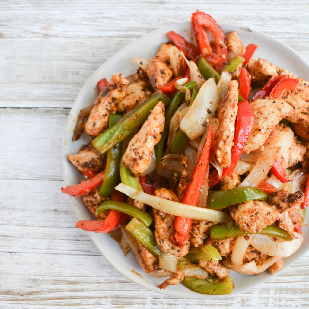 close up on a heaping plate of sheet pan chicken fajitas