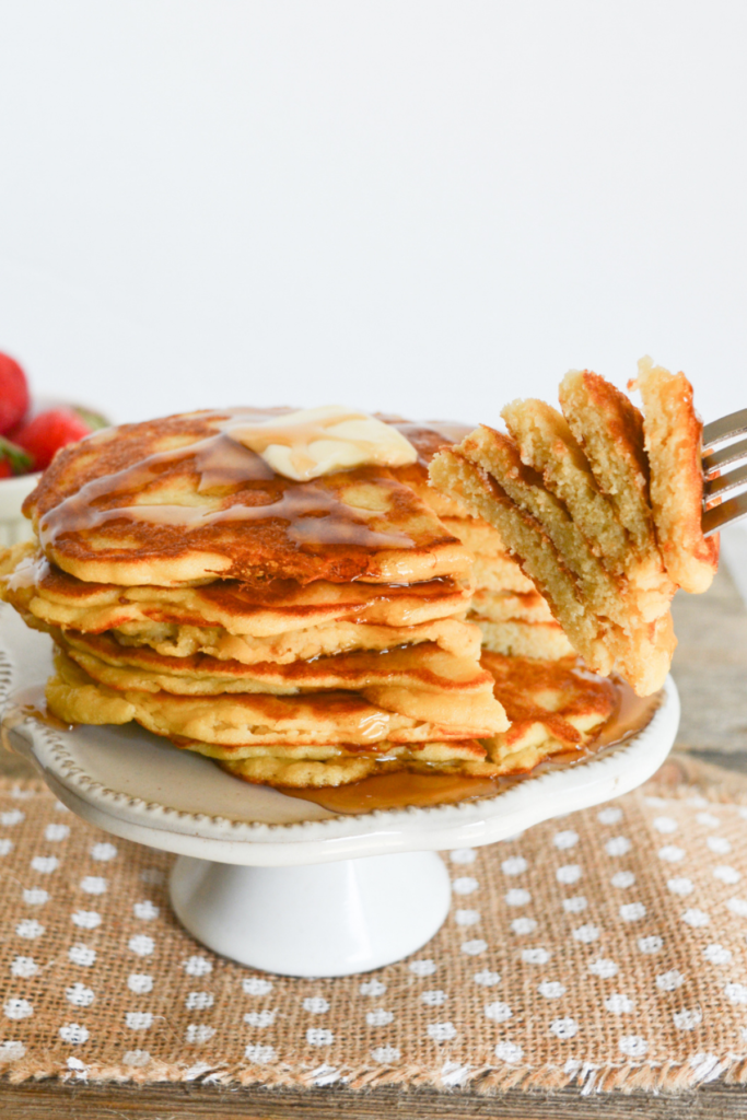 close up on a stack of coconut flour keto pancakes, covered with sugar free syrup and a pat of butter, with a slice of the stack being taken away with a fork