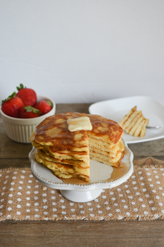 stack of coconut flour keto pancakes, covered with sugar free syrup and a pat of butter, with a slice of the stack taken out and placed in the background