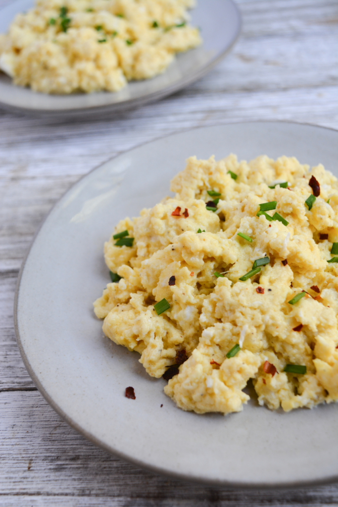 plate of fluffy scrambled eggs garnished with chopped chives and crused red pepper