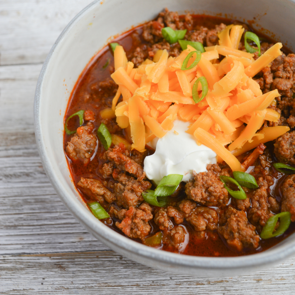 close up on a bowl of keto chili topped with green onions, sour cream, and shredded cheddar cheese