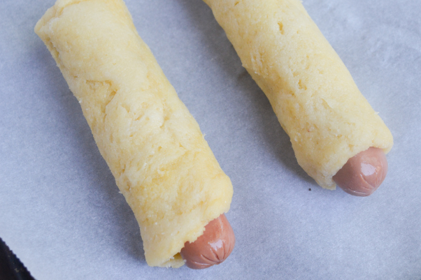 keto pigs in a blanket step 3 - wrapping the hot dogs with fathead dough