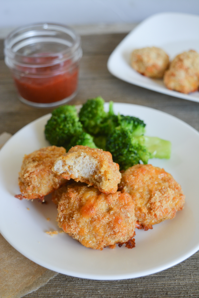 plate of keto chicken nuggets and broccoli with a bite taken out of one of the nuggets